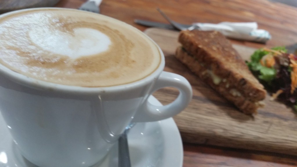 Cheese, tomato and pesto toasted sandwich and a cappuccino make for a delicious light snack.